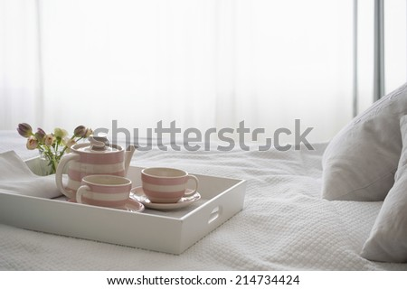 Pink striped teaset on breakfast tray in bedroom - stock photo