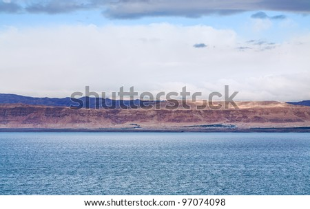 pink sunrise on Dead Sea coast and view of Jerusalem in sunbeam - stock photo