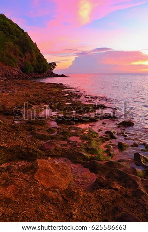 Pink sunset exotic tropical rocky coastline. Purple clouds and vivid evening with sea water reflection. Quiet island vacation.