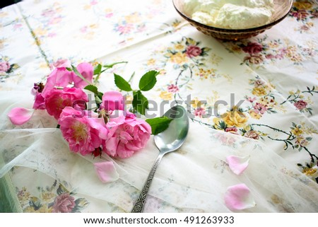 Pink tender flowers on summer outdoor dinner table closeup
