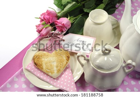 Pink theme Happy Mothers Day breakfast in bed with tea cup and tea pot, roses and heart shape toast with white copy space for your text here. - stock photo