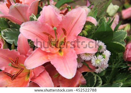 Pink tiger lilies and roses in a bridal arrangement