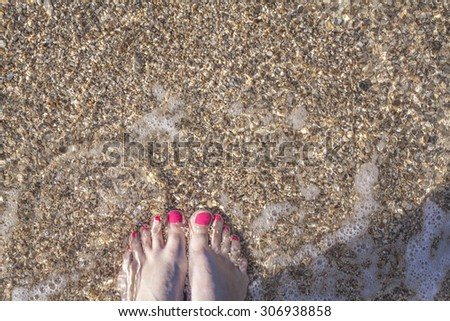 Pink toes, sea and sand - stock photo