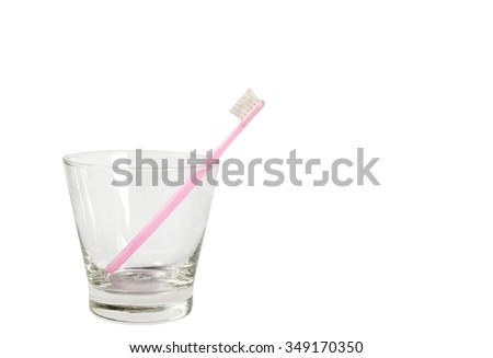 Pink toothbrush in the glass on the white background.
