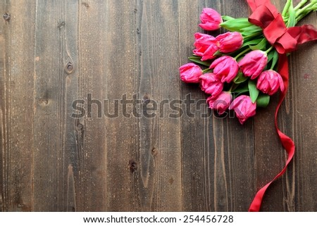 Pink tulips bouquet with red ribbon on dark wood background - stock photo