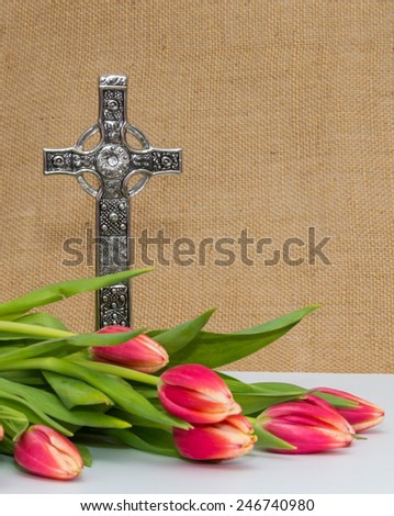 Pink tulips in front of a silver Celtic Cross - stock photo