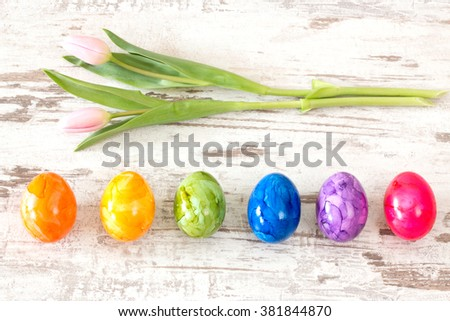 Pink tulips with Easter eggs on bright rustic wooden background