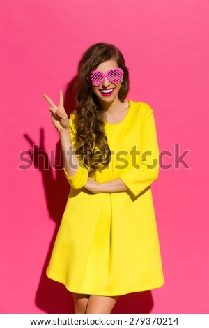 Pink Victory. Beautiful girl in yellow mini dress and pink heart shaped sunglasses posing with peace hand sign. Three quarter length studio shot on pink background. - stock photo