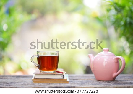 pink vintage  teapot  with a cup of glass tea and notebooks  - stock photo