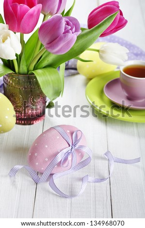 Pink, violet and white tulips in a glass vase with easter eggs on wooden background