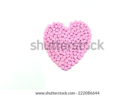 pink vitamin c of  heart shape on white background - stock photo