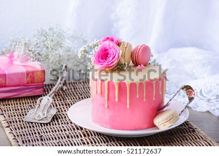 Pink wedding cake with French macarons and flowers on top, vintage pastry tongs and present box