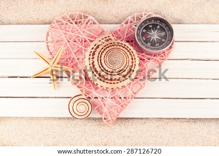 Pink wicker heart and few marine items on a wooden planks over sandy background. - stock photo