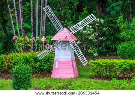 Pink Wind Generators Turbines in Garden. - stock photo