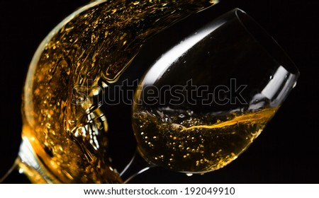 pink wine being poured into a wineglass on black background
