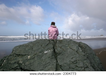 Pink woman on rock by ocean - stock photo