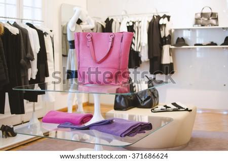 Pink women handbag in a clothing fashion store. - stock photo