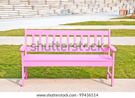 Pink wood chair on the green grass