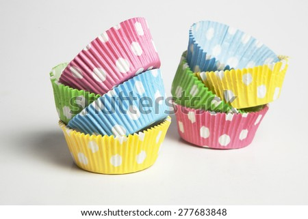 Pink,yellow,blue and green cupcake liners in white background - stock photo