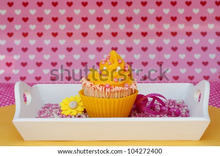 pink yellow cupcake on a white plateau with romantic heart background - stock photo