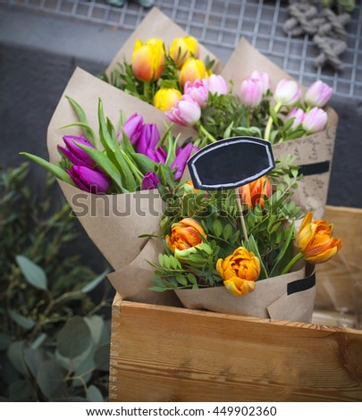 Pink, yellow, orange colorful tulips closeup on sale in the flower market - stock photo