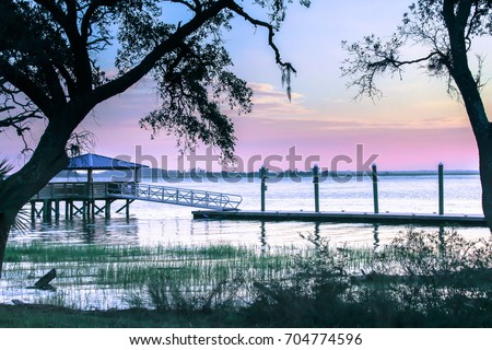 Pinkish purple Sunset at Bloody Pointe on Daufuskie Island, SC at a pier on a desolate island off the coast of South Carolina. Silhouette trees in foreground and a dock/ Daufuskie September sunset