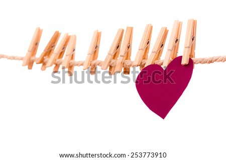 pinks paper heart and many clothespins hanging on a rope clothesline isolated on white - stock photo