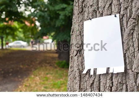 Pinned blank vertical paper label on a tree