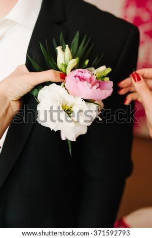 Pinning a Boutonniere for groom on wedding day
