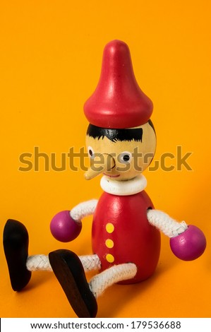 Pinocchio Toy Statue on a Colored Background - stock photo