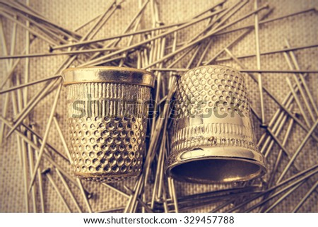 Pins and thimbles on a piece of cloth seen from above. Vintage style. Horizontal image.