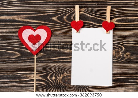 Pins, red hearts, blank card on wooden background
