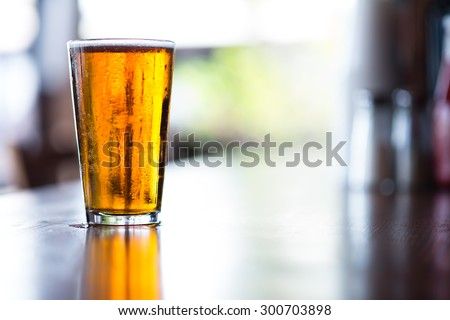 Pint glass of India Pale Ale on long bar in afternoon - stock photo