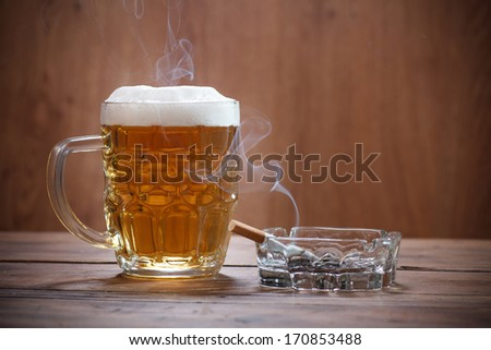 Pint of Beer and a lit cigarette