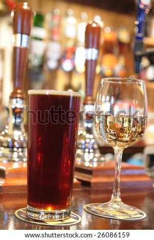 pint of beer and glass of white wine on bar in a pub
