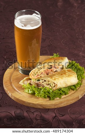 Pint of beer and shawarma over wooden dish