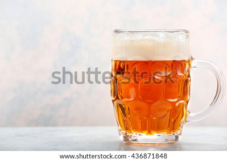 Pint of beer on blue background with space for text