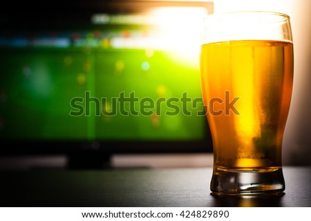 Pint of beer on the table in front of television show off football.  - stock photo