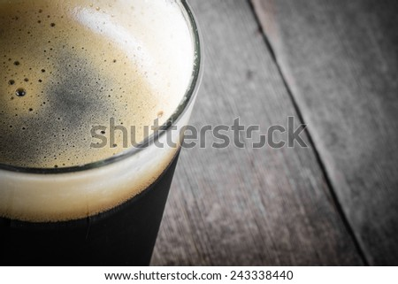 Pint of Dark Beer on Wood Background - stock photo