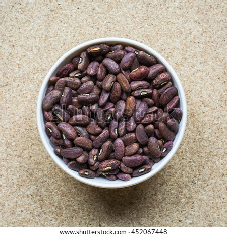 Pinto beans. Colorful various beans or lentils and whole grains seeds or cereal in white cup on wood background. - stock photo