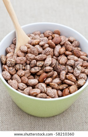 Pinto beans with a wooden spoon in a green bowl - stock photo