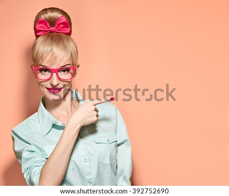 Pinup beauty woman in stylish glasses shows finger, idea. Attractive funny blonde nerd girl smiling. Pinup hairstyle, trendy glasses, pinup bow and makeup. Unusual playful, expression.Vintage, on pink - stock photo