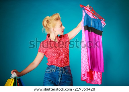 Pinup blond girl young woman in retro style buying clothes pink dress. Client customer holding colorful paper shopping bags on vibrant blue. Retail and sale. Studio shot. - stock photo