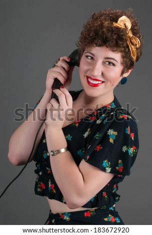 Pinup Girl Smiles While on Black Telephone - grey background - stock photo