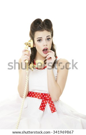Pinup girl with her hair down in retro victory rolls, talking on the phone and looking surprised.