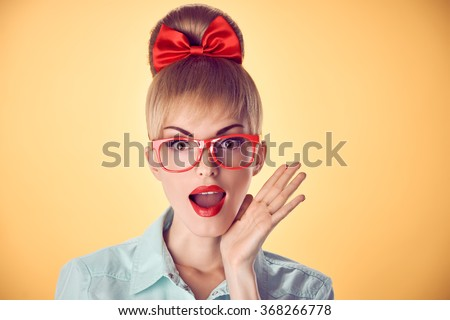 Pinup nerd woman in stylish glasses surprised. Attractive blonde nerd girl, open mouth. Pinup hairstyle, trendy nerd glasses, pinup bow,makeup. Unusual playful surprised expression. Vintage - stock photo