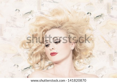 Pinup portrait of a beautiful sexy blond girl with classic makeup and short wavy blond hair on vintage design background - stock photo
