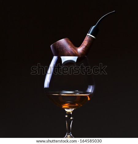 pipe and snifter with brandy on  black background - stock photo