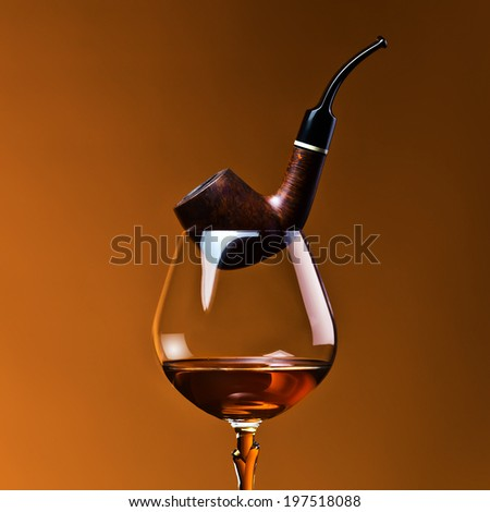 pipe and snifter with brandy on  dark background - stock photo
