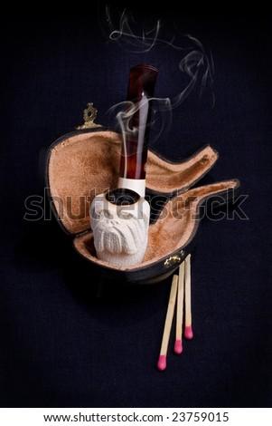 Pipe case match close up smoke background flame ashes smoking - stock photo